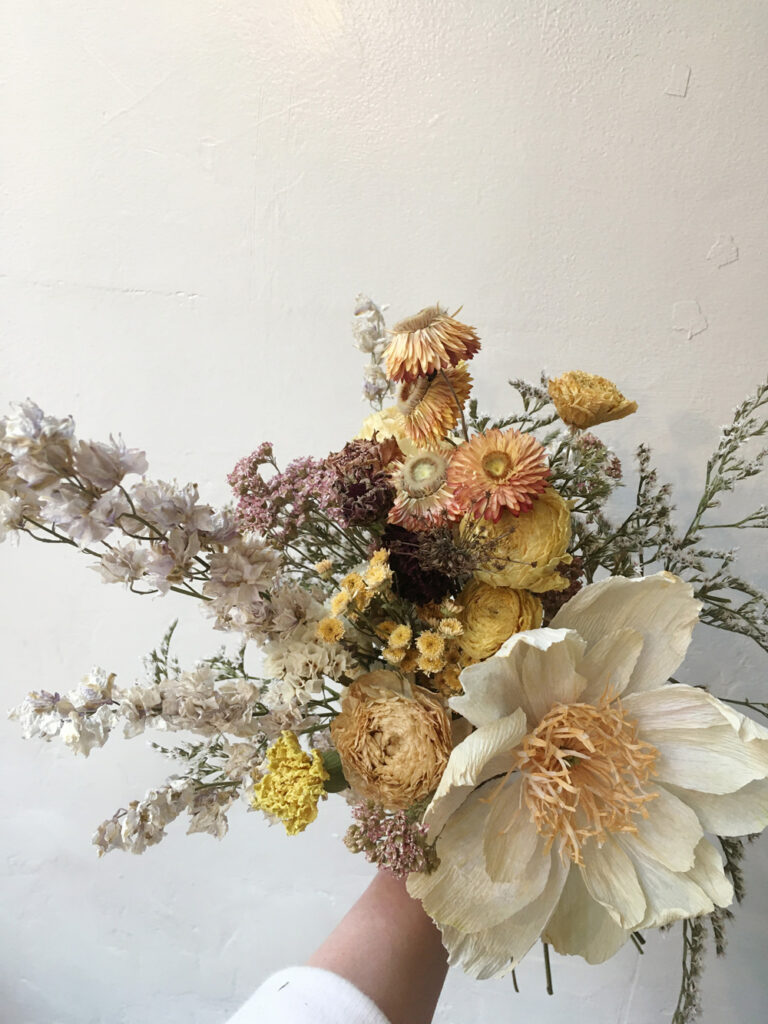 wedding bouquet in warm tones with organic dried flowers and a paper flower made by Wilder Antwerp